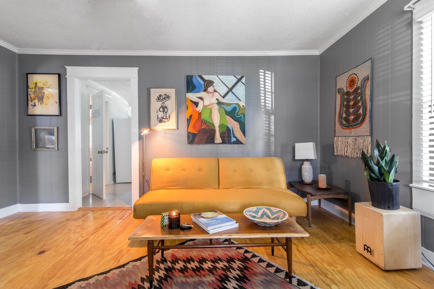 Living room space with Scandinavian light wood floors, collected art and midcentury furnishings. Yellow sofa folds down into a full-sized bed.