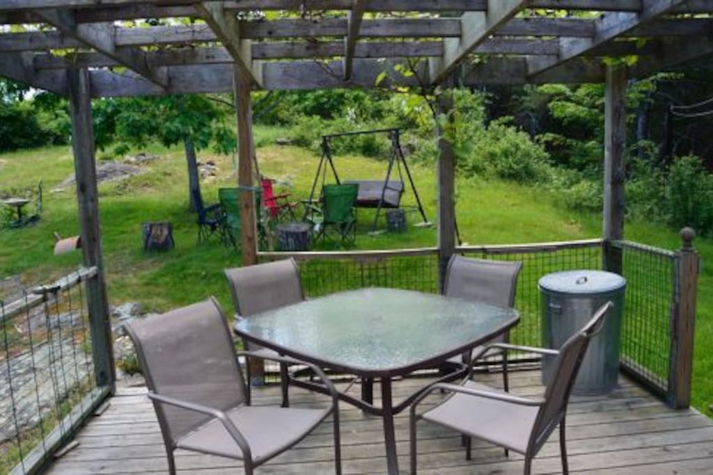 Deck for outside dining and glider and chairs under the oak tree with view of the gardens