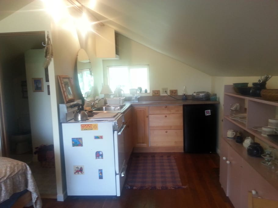 Bathroom to left of stove; fuller view of kitchen with nice storage for dishes and drygoods to right.