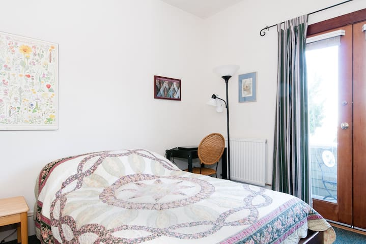 Your bedroom with view onto guest room balcony. Desk and desk lamp in corner.