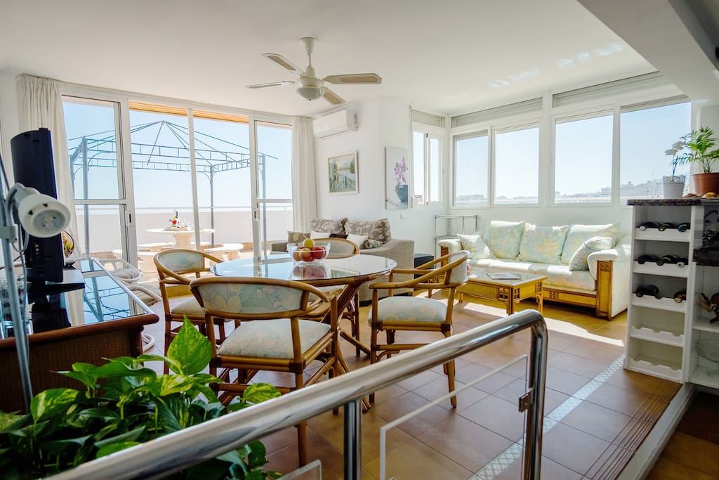 Luminoso salón comedor con aire acondicionado, dos sofás mesa comedor, sillones y televisión.