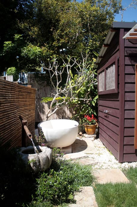 Relax in the bath under the frangipani tree.