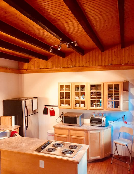 Kitchen with all the amenities, utensils and cooking ware you need to make yourselves at home.  Open plan with dining table.