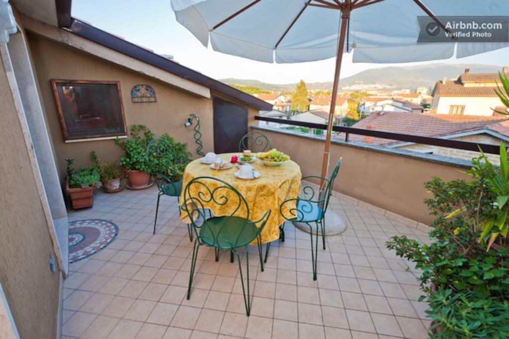 nel terrazzo con vista su Assisi si può comodamente gustare una ricca colazione seduti all'ombra