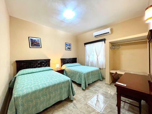 Segunda recámara con dos camas matrimoniales y aire acondicionado.