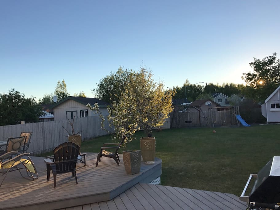 View out into the yard in late afternoon/evening.  There are pear trees, apple trees)multiple kinds, and a cherry tree in the back yard.  This area is perfect having bbqs, relaxing on deck chairs, enjoying a nightly fire, playing catch or just sitting outside to enjoy the fresh air.