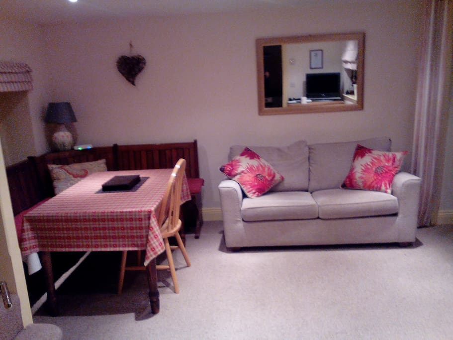 Lounge with TV, dining table and traditional pugh seating.