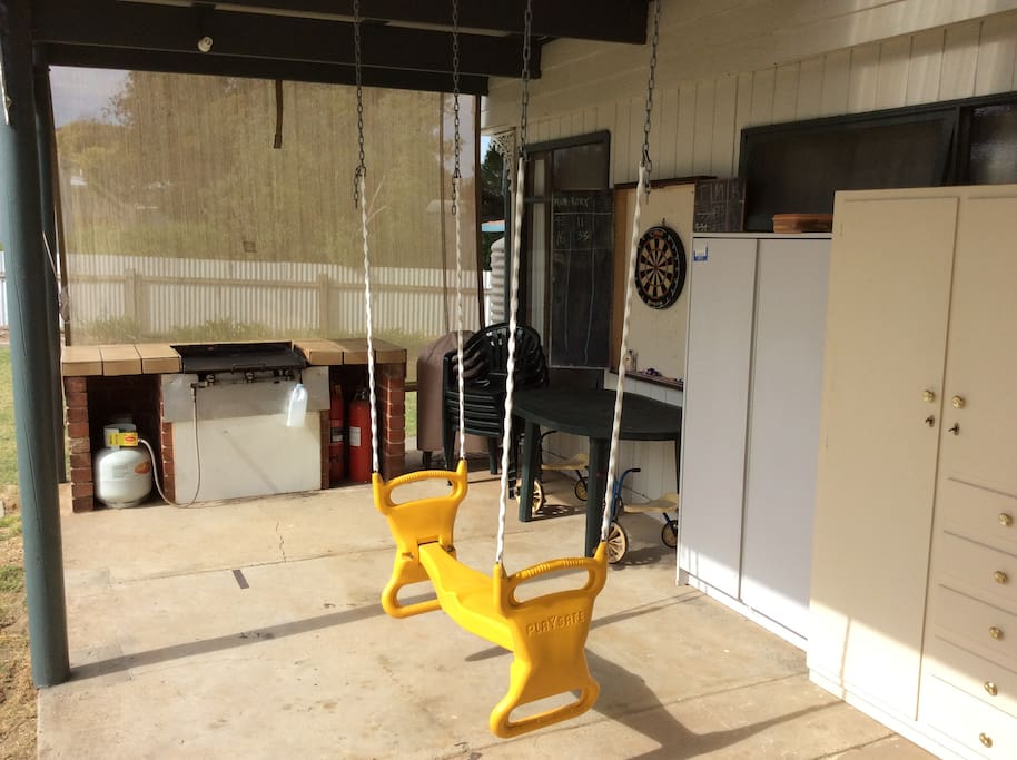 outdoor living area with BBQ dart board and childrens swings