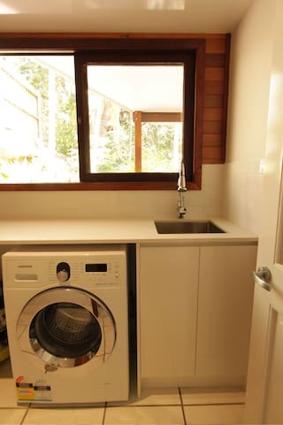 Laundry with stone bench tops and brand new washer and dryer. Like the tap and rain forest views