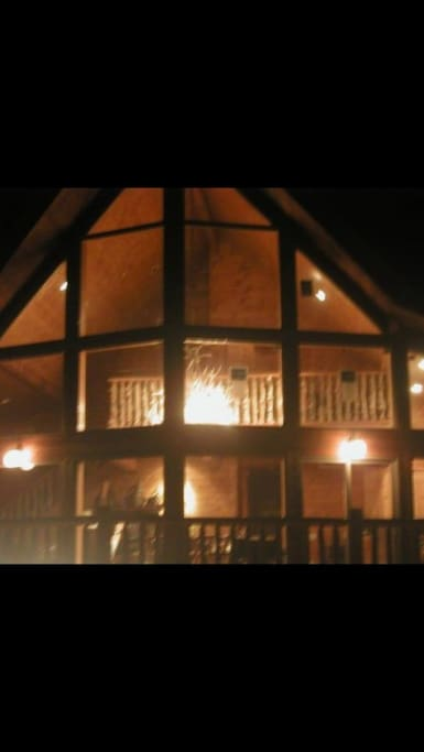 A frame cedar house with all glass windows and a glass door leading to a very big deck..