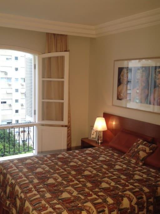 Suíte com amplas janelas superiores e inferiores para rua arborizada. Vista de frente do 8o andar.