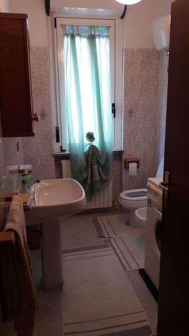 Bagno unico, in camera da letto matrimoniale con doccia dietro la porta e lavatrice
