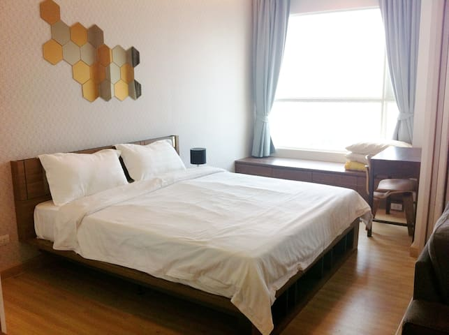 the bedroom with a desk and a bench by the window. You can see the Grand Palace from this window. Great view at night