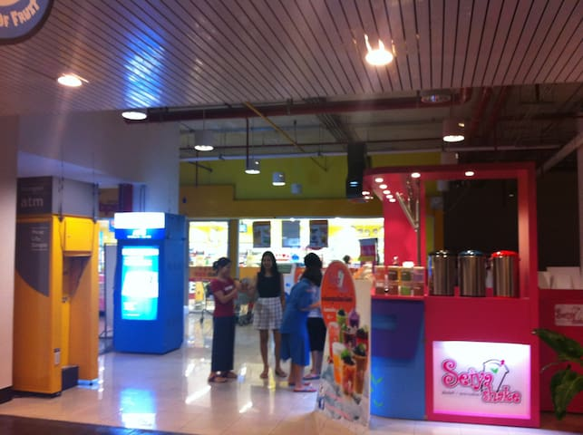 In front of the supermarket on the ground level with ATMs and bubble tea stall. (Floor 1-4 of the building is a plaza with shops and restaurants.)