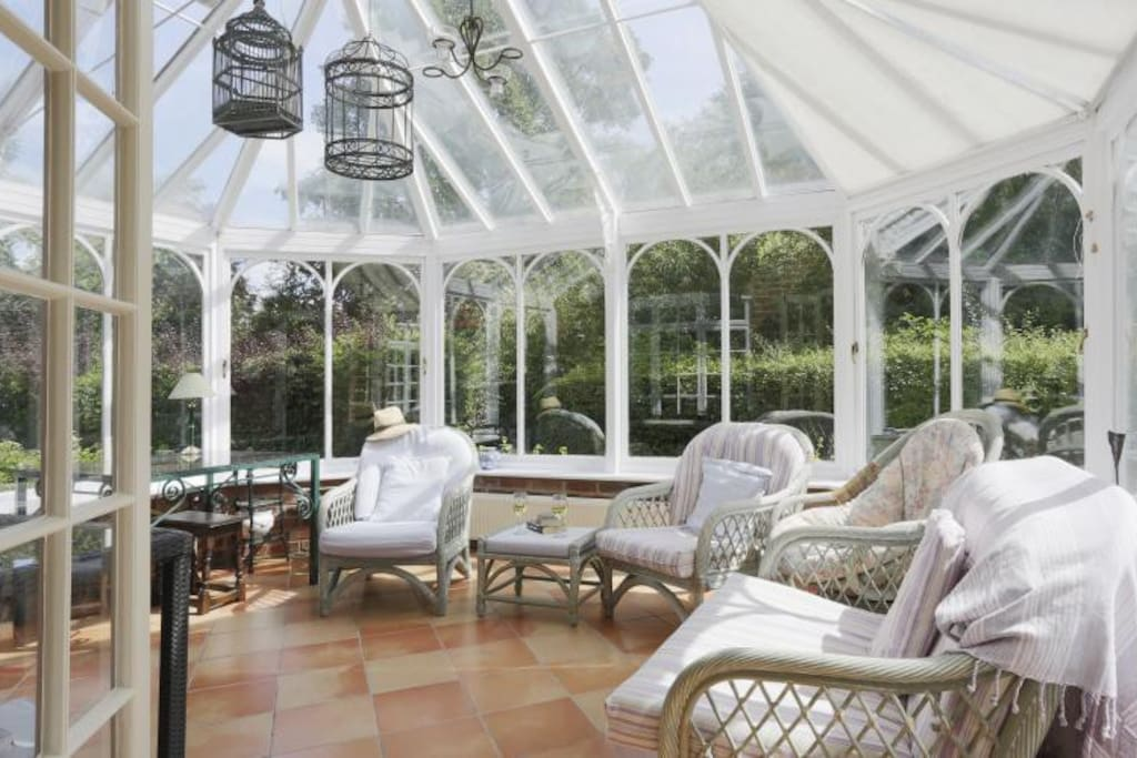 Comfortable chairs in the sun bathed conservatory.