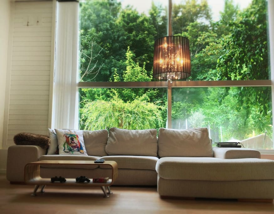 Our livingroom with panorama windows overlooking the lush green garden.