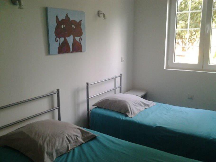chambre à 2 lits avec une commode et un portant