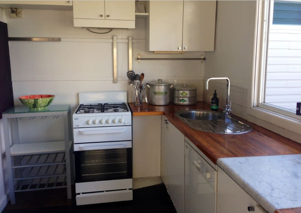 Kitchen with gas stove, fridge, cooking utensils
