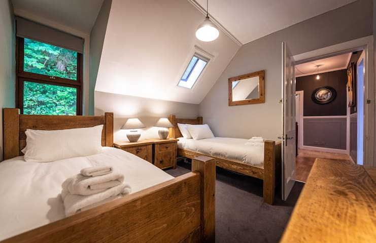 The twin bedded room, with bespoke hand made wooden beds, bedside tables and dressing table. Luxury Hungarian Goosedown bedding