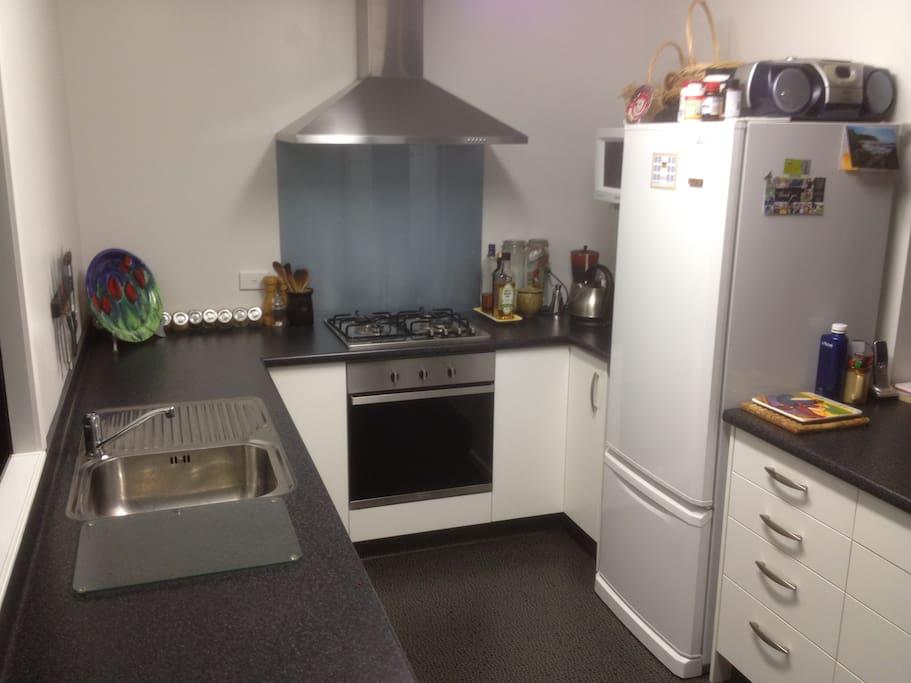 Modern kitchen - gas hob, microwave, fridge/freezer, filtered rainwater.