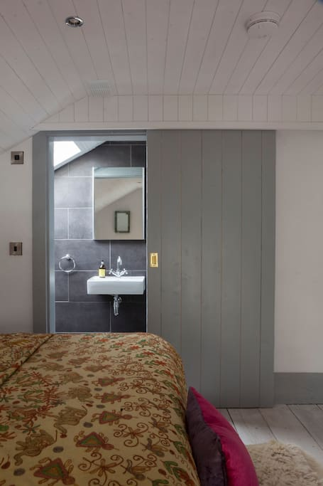 The ensuite bathroom of the Hayloft bedroom. Each room has a super-king sized bed with crisp white lined, quirky rustic interior and ensuite bathroom.