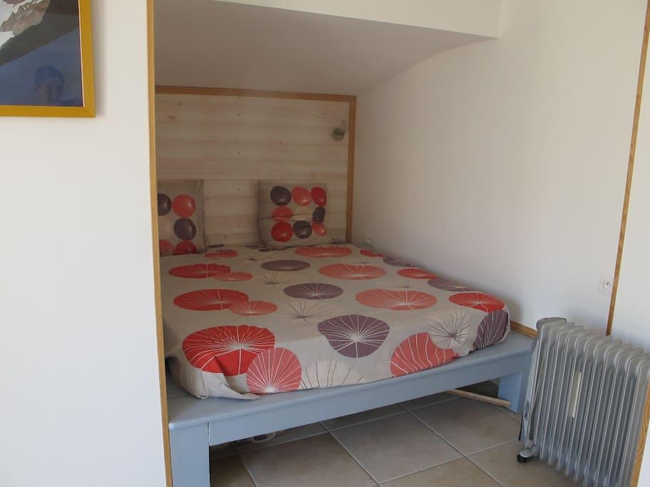 Le lit double en alcôve avec canapé, bureau et dressing