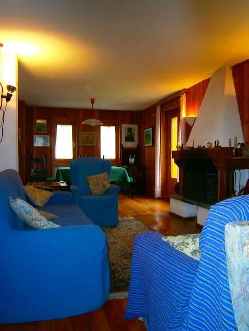 A sinistra dell'ingresso, l'ampia zona giorno con tavolo da pranzo, divano e due poltrone di fronte al camino, televisore.