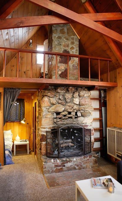original stacked stone fireplace with open beamed ceiling and sleeping loft above.
