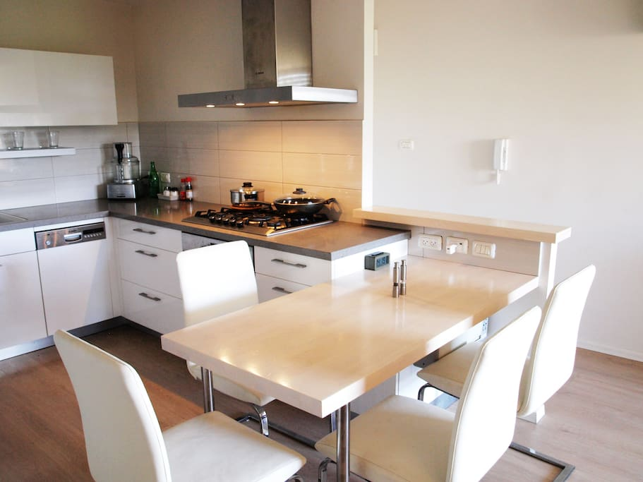 Fully equipped modern kitchen with all new appliances. Dining table sits a party of four.