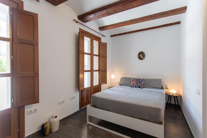 Habitación matrimonial con una cama doble + una cama individual. Dos balcones con mesa y sillas +  vistas al otro lado del casco histórico.