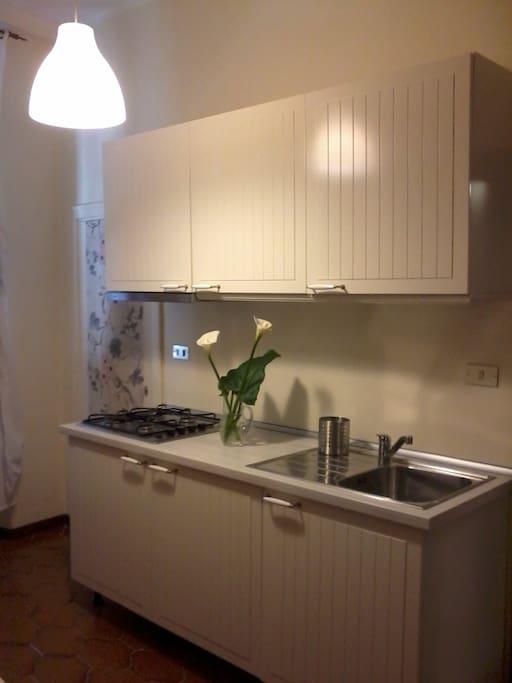 Cucina completa di frigorifero, piano cottura e lavello.