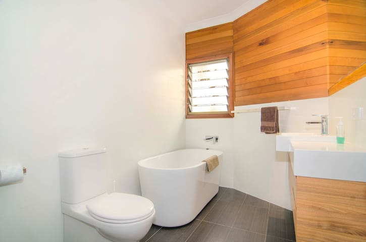 The Main Bathroom with free standing bath and shower wrappend in warm cedar wood
