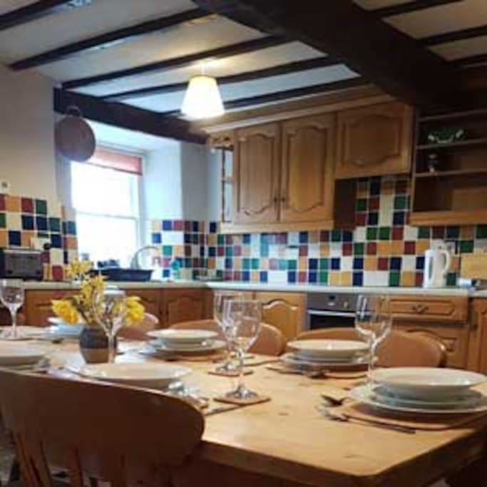 The kitchen adjacent to the farmhouse dining table