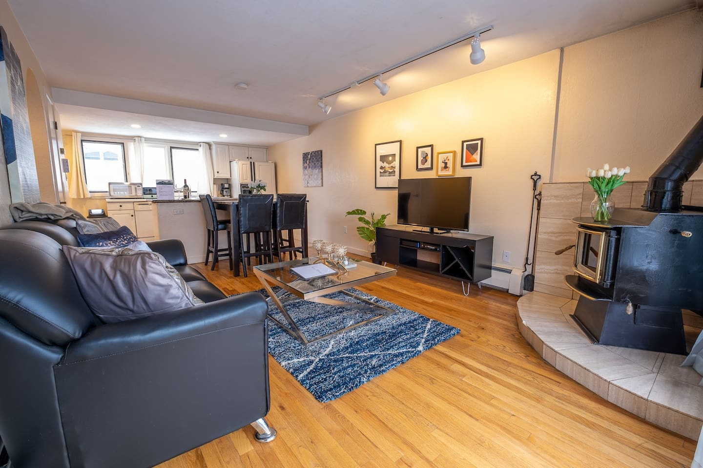 Light, bright living room to cozy up in. Enjoy the heat of the wood stove!
