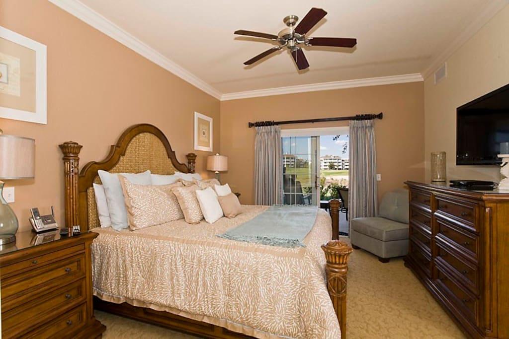 Luxury master bedroom with king size bed, ceiling fan, flat screen HDTV, walk in closet, wall safe, with direct access on to the large relaxing patio