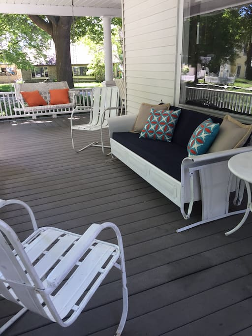 Front porch with antique glider, rockers, and hanging swing.