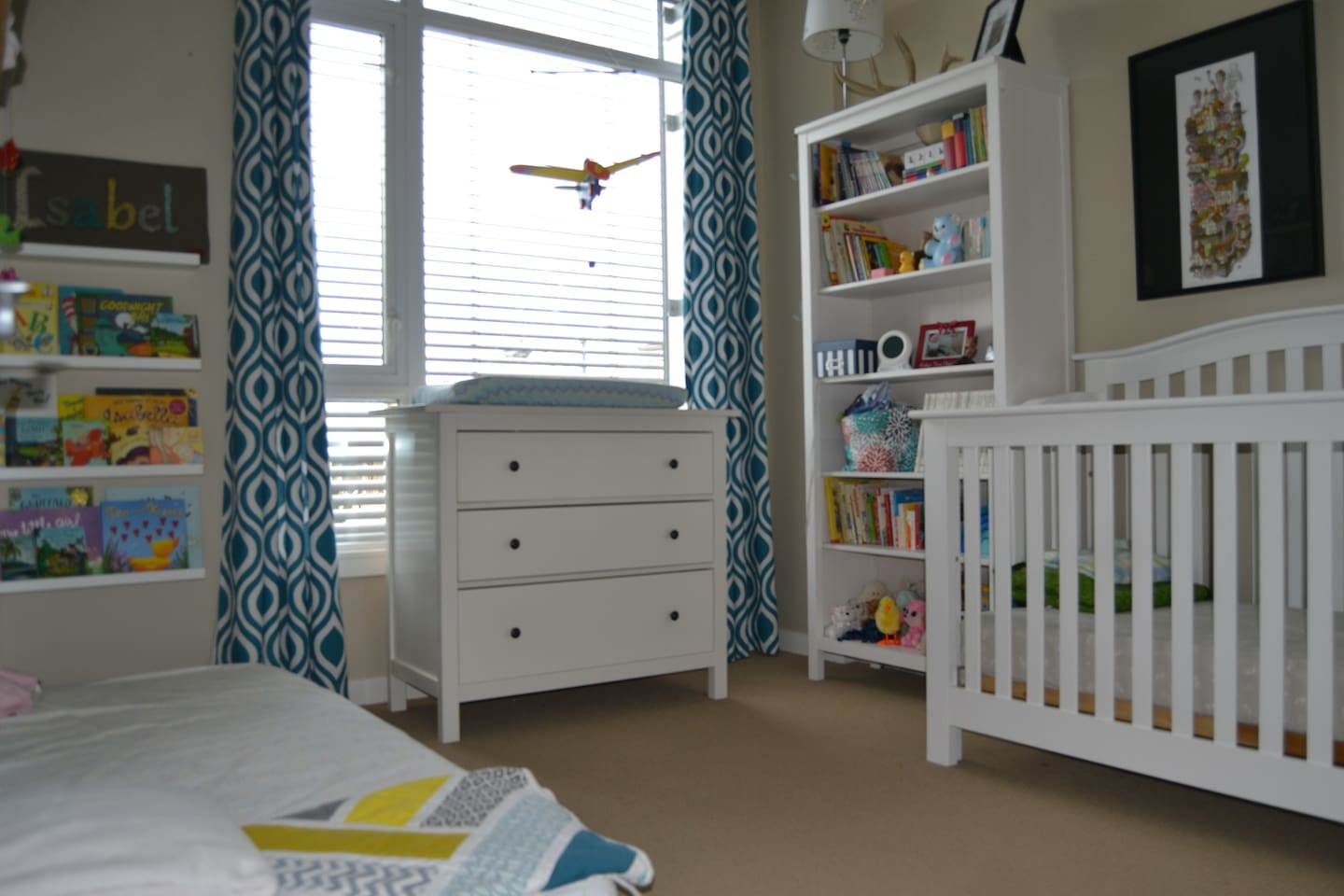Kids room with single mattress and a crib.