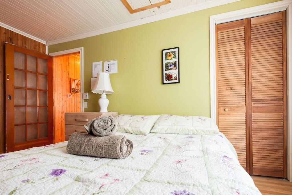 Chambre double comprenant lit avec matelas confortable, commode, chaise, miroir, lampe, grande fenêtre avec vue sur le fleuve