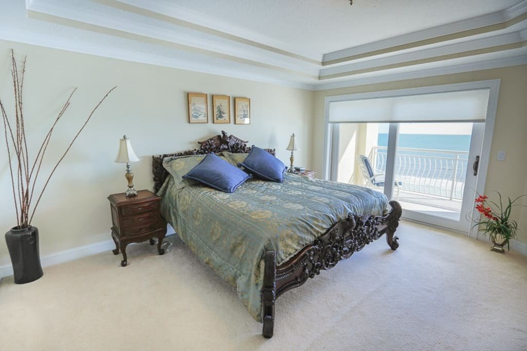 master bedroom overlooking balcony and ocean