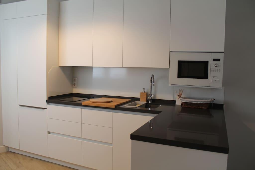 Cocina abierta, completamente equipada con frigorífico-congelador, vitroceramica de inducción, lavadora-secadora, microondas, tostadora, calentador de agua eléctrico y menaje completo.