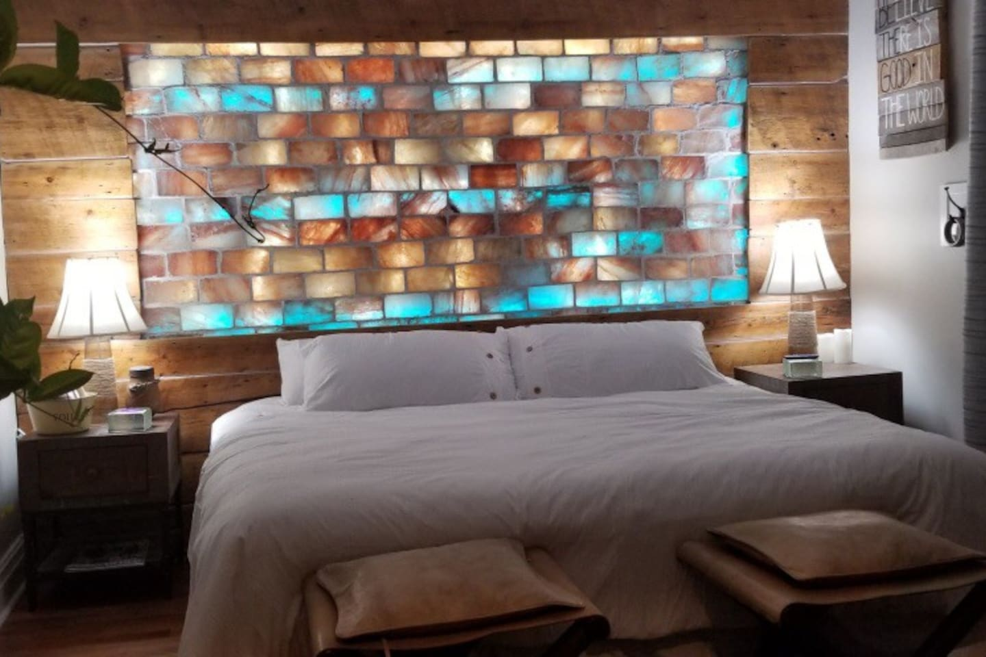 Himalayan Salt Wall as Headboard, king size bed with pillow topper mattress cover, 4 king size pillows, custom side tables and luxury lamps, Full wardrobe with large clothes hanging area, and big deep drawers for clothing custom one of a kind leather foot stools top off the room