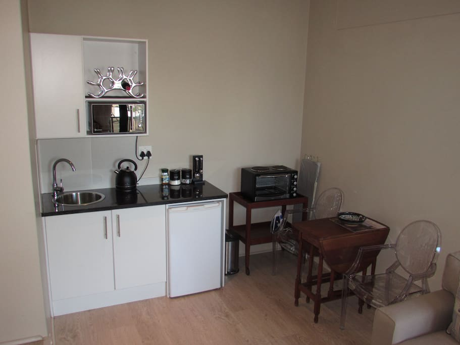 Kitchen with kettle, toaster, iron, ironing board, microwave and two plate stove