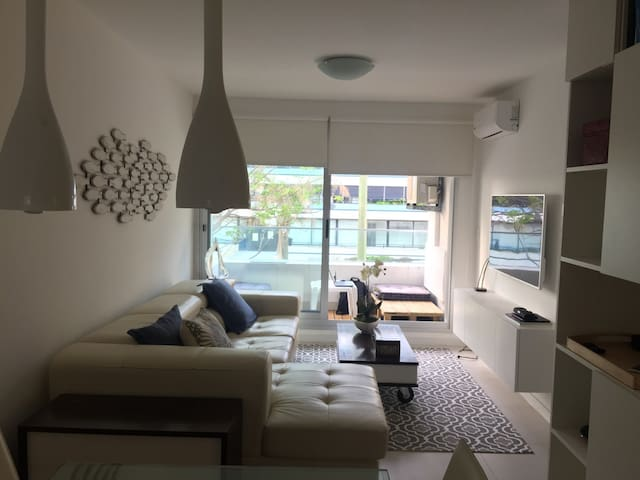 Living Room. Super confortable sofa. Turns into a raised double bed. AC, TV (built in-netflix), Apple TV (entertainment system), Bluetooth Speakers. Strong, Fast WiFi in all the apartment. Noise Cancelling Double Windows.