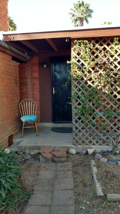 Welcome! Your private entrance and porch are surrounded by vines, flowers, and trees.