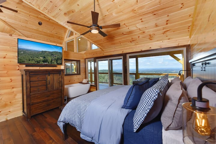 """King adjustable bedroom with 55"""" TV, soaking tub and panoramic views."""