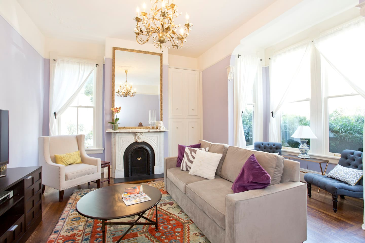 Living room features towering ceilings, original Victorian details and gorgeous bay window.