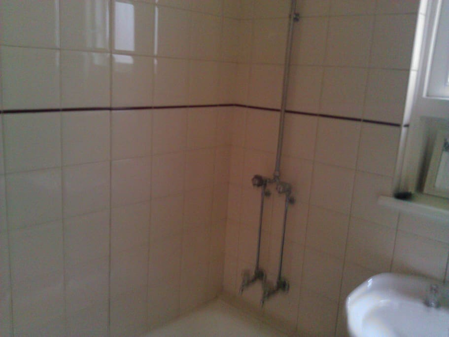 Clean tiled bathroom with shower over bath.