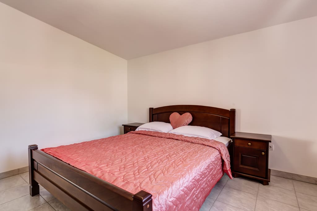 Bedroom 1 with comfortable double bed with night stands next to the bed.