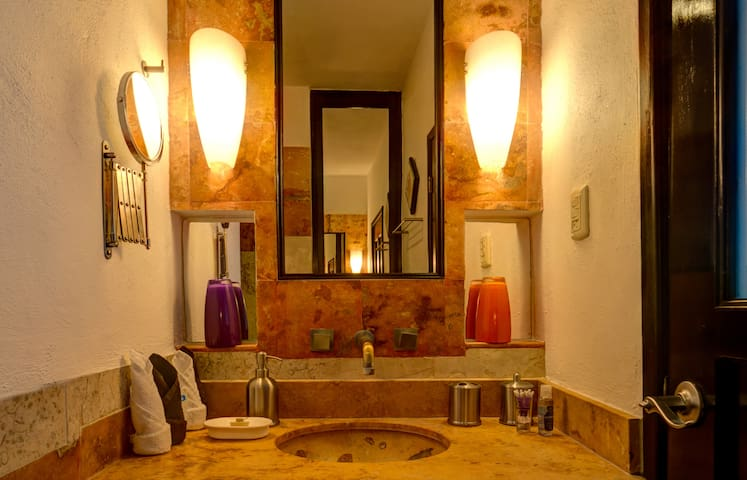 Private stone-tiled bath with shower