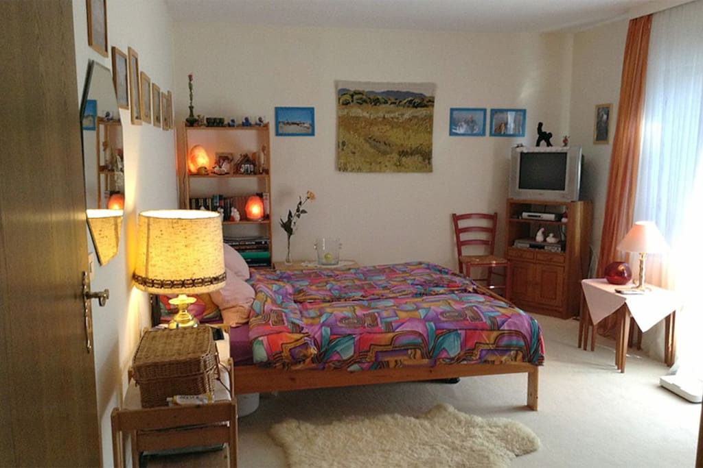 Your bedroom with double-size bed, TV and big windows to the garden.